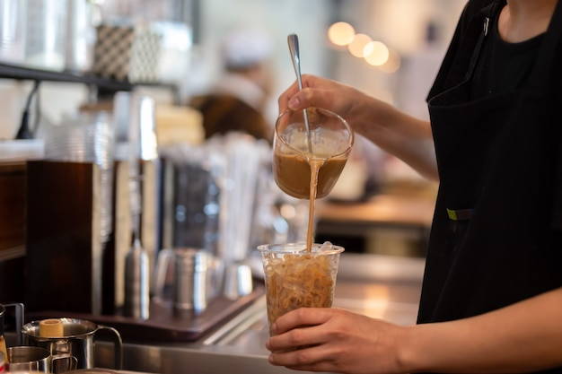 Barista vrouw barista koffie gieten in afhaalmaaltijden glas in de koffieshop.