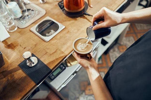 Barista-vrouw die cappuccino maakt, vrouw die koffiedrank voorbereidt. koffiekopje met latte art.