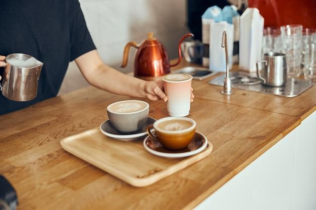 Barista-vrouw die hier cappuccino maakt in kopjes en te gaan, vrouw die koffiedrank voorbereidt. koffiekopje met latte art.