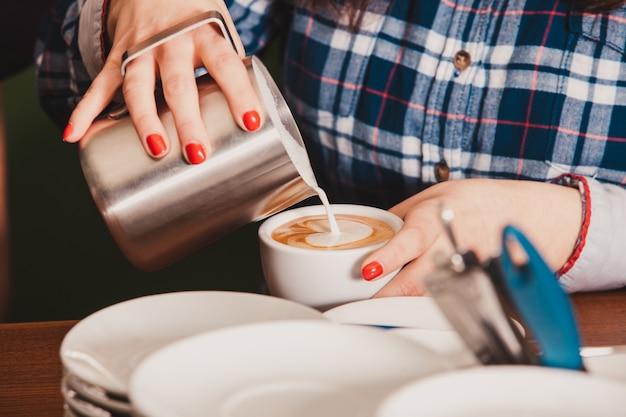 Barista zet een kopje latte art koffie, schenkt melk in met schuim