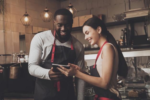 Baristaman en vrouw die een tablet bekijken