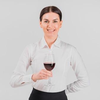 Barkeeper die en glas wijn glimlacht houdt