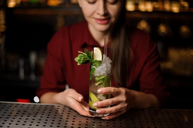 Barmaid staat aan de bar en houdt een kant-en-klare mojito vast