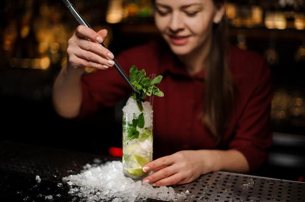 Barmaid voltooit het ontwerp van de mojito-alcoholcocktail