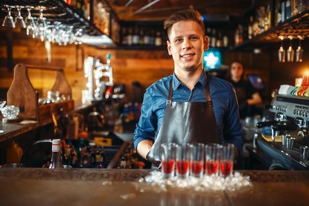 Barman aan het loket met glazen die in ijs staan