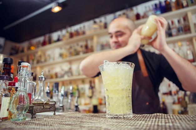 Barman aan het werk. cocktail in shake schudden.