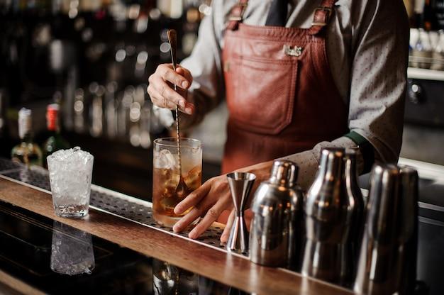 Barman afkoelen cocktailglas mengen ijs met een lepel