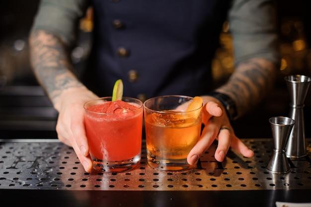 Barman bereidde twee cocktails van rood en oranje voor de bar
