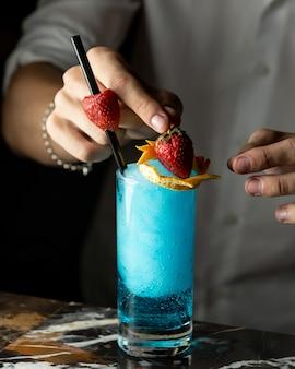 Barman bereidt blauwe cocktail gegarneerd met sinaasappelschil en aardbeien