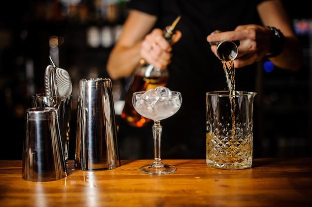 Barman bereidt een amberkleurige alcoholische cocktail met behulp van een kristalglas met ijs