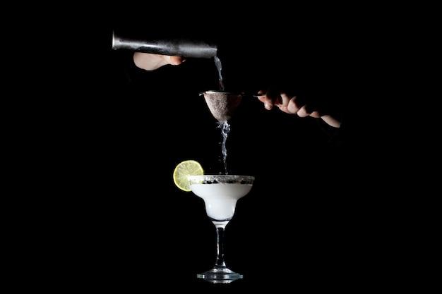 Barman bereidt een klassieke margarita voor, hij giet een cocktail