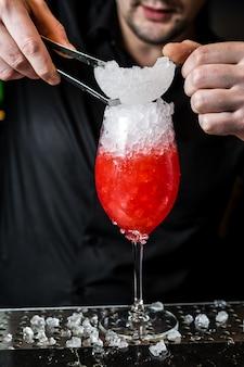 Barman bereidt margarita-cocktail, close-up voor