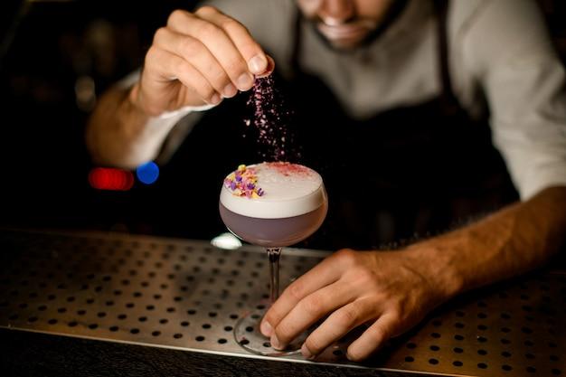 Barman besprenkelen op de cocktail versierd met bloemblaadjes een geraspte bloemen
