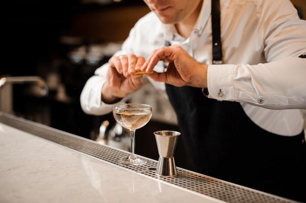 Barman besprenkelen sap van citroenschil in een cocktailglas