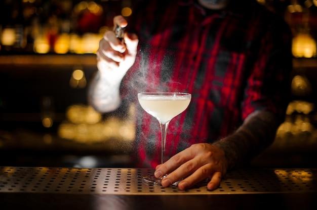 Barman besprenkelt elegant cocktailglas met lichte en smakelijke alcoholische drank met bitter op de bar