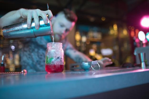 Barman cocktail aan balie voorbereiden