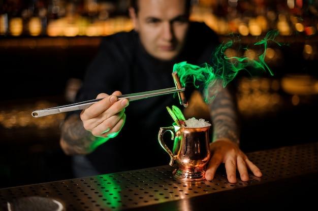 Barman die aan de cocktail in het kuiperglas toevoegt met een gedroogde oranje aromatische gerookte kaneel met een pincet in het groene licht op de toog.