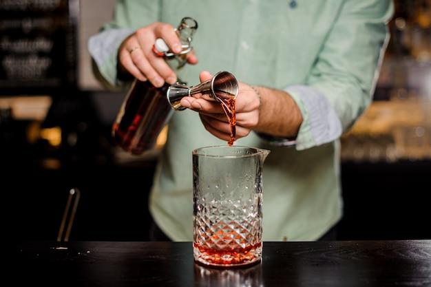 Barman die alcoholische cocktail, metaaljigger en baromgeving maakt