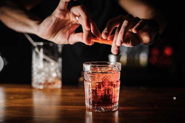 Barman die alcoholische cocktailnegroni van roze kleur met ijs voorbereidt