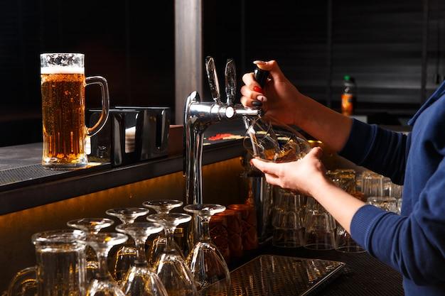 Barman die bier in het glas in bar gieten