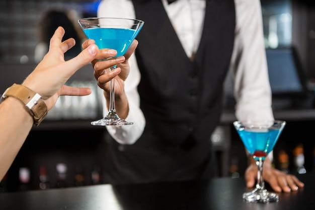 Barman die blauwe cocktail dienen bij barteller in bar
