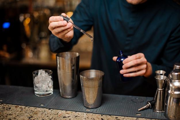 Barman die blauwe kleurstof toevoegt aan een schudbeker die zomercocktail maakt
