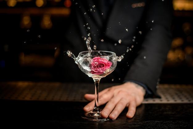 Barman die bloem in een alcoholcocktail toevoegen