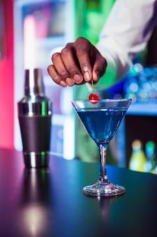 Barman die cocktail met kers op barteller versieren in bar