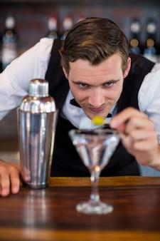 Barman die cocktail met olijf versieren