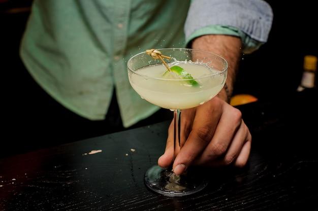 Barman die de cocktail met kalk dicht omhoog maken
