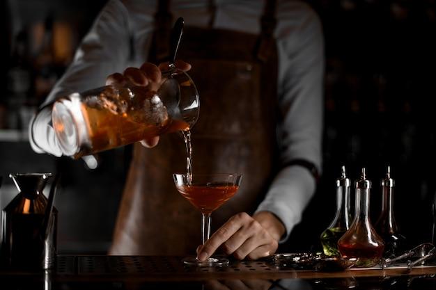 Barman die een alcoholcocktail van zeef gieten
