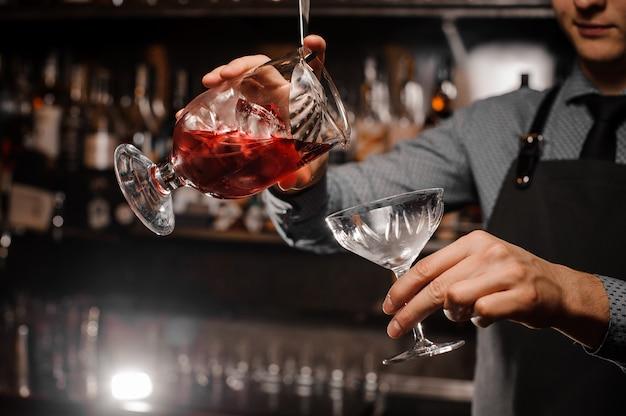 Barman die een alcoholische cocktail in het cocktailglas giet