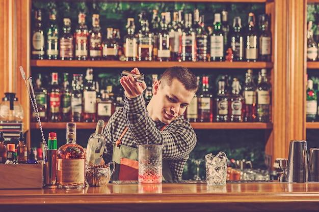 Barman die een alcoholische cocktail maakt aan de toog op de bar