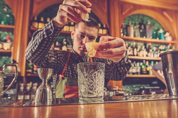 Barman die een alcoholische cocktail maakt bij de bar aan de bar