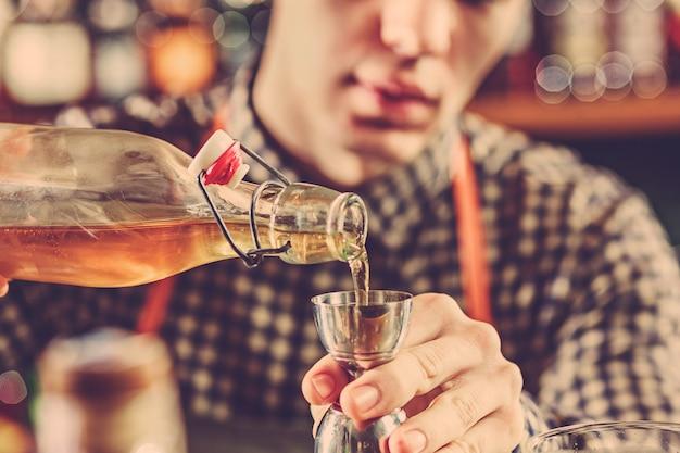 Barman die een alcoholische cocktail maakt bij de barteller