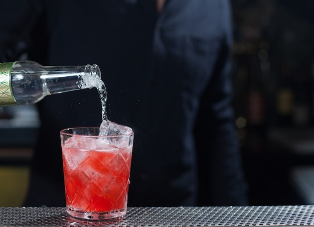 Barman die een alcoholische cocktail maakt, een zomercocktail in de bar