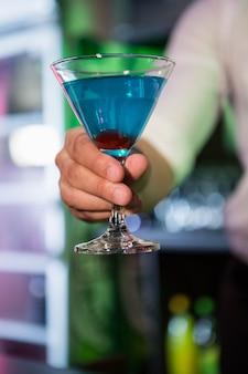 Barman die een blauwe martini in bar dienen