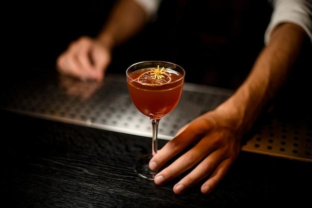 Barman die een cocktail in het glas met een gekarameliseerde citroenplak serveert