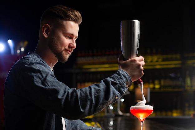 Barman die een cocktail maakt met een shaker
