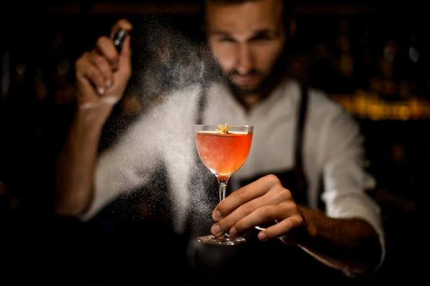 Barman die een cocktail serveert met een gekarameliseerde schijfje citroen en een beetje gele bloem die erop sproeit