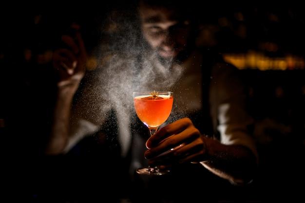 Barman die een cocktail serveert met een schijfje citroen en een kleine gele bloem die er in het donker op sproeit