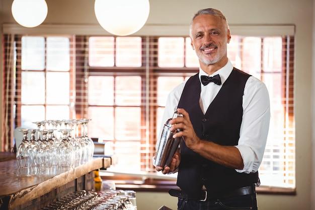 Barman die een cocktaildrank in cocktailshaker mengen