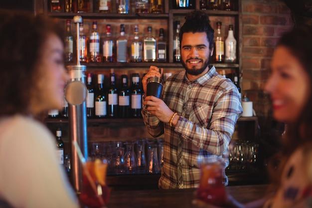 Barman die een cocktaildrank in cocktailshaker mengt