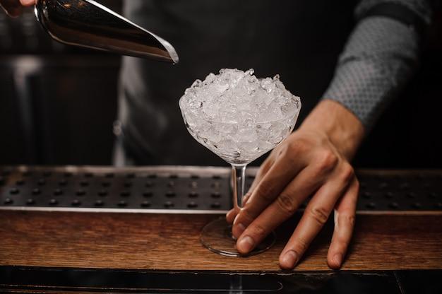 Barman die een cocktailglas houdt dat met ijs wordt gevuld