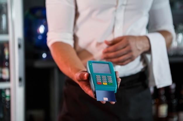 Barman die een creditcard accepteren bij de bar in de bar