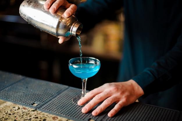 Barman die een frisse en zoete blauwe cocktail in een glas giet