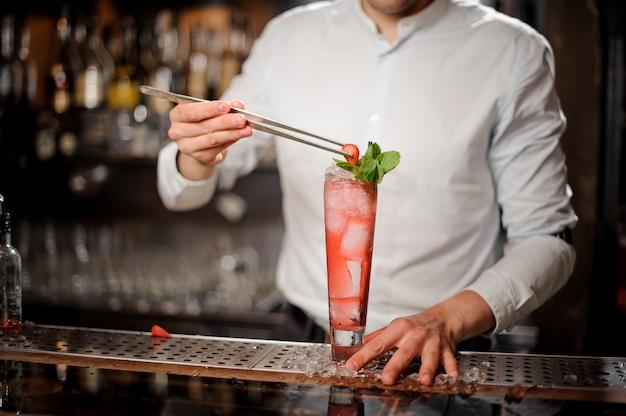 Barman die een glas verse en zoete de zomercocktail van aardbeimojito met een bes verfraait