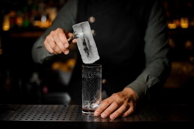 Barman die een groot ijsblokje in een leeg glas op een toog zetten