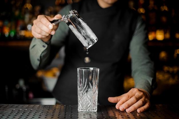 Barman die een groot ijsblokje in een leeg glas zet