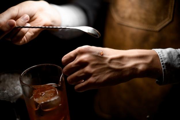Barman die een lepel houdt en een druppel op de hand legt